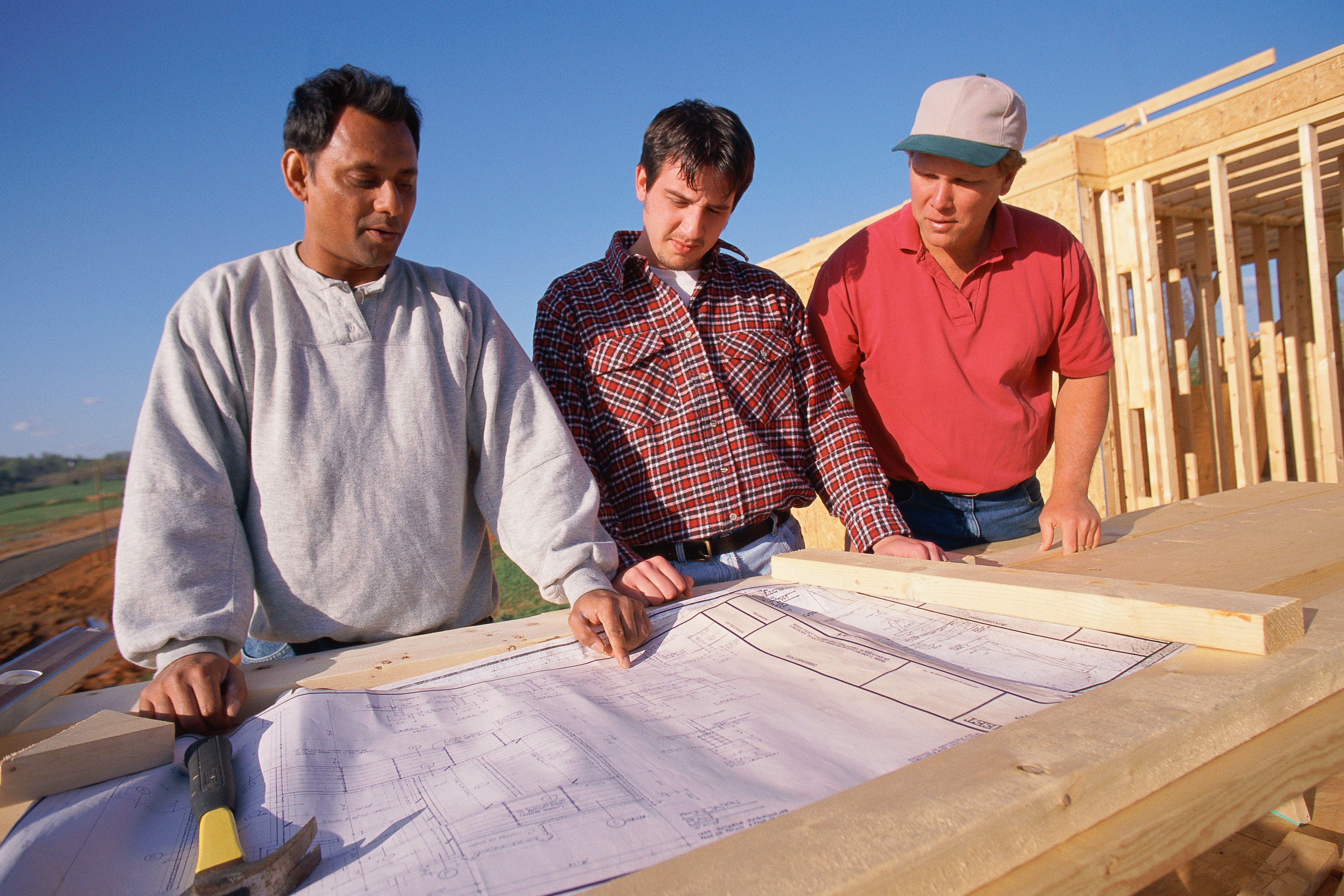 photo of men looking at house plans