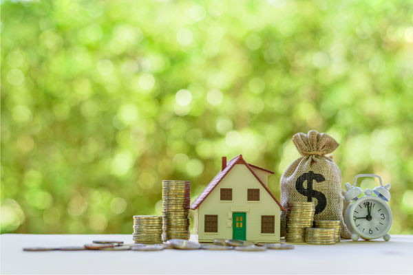 Refinance your home mortgage concept with coins, alarm clock and bag of money around a small house